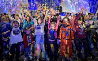 Στις ενθουσιώδεις εκδηλώσεις για τη μεγάλη επιτυχία της NASA συμμετείχαν και παιδιά κρατώντας αμερικανικές σημαίες, ενώ τη χαρά του δεν έκρυβε και ο βασικός ερευνητής των «Νέων Οριζόντων», δρ Αλαν Στερν (στο μέσον της φωτογραφίας με υψωμένο το χέρι).