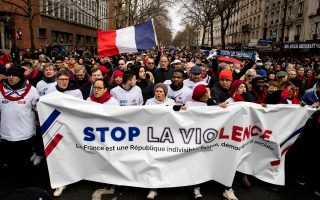 Πανό κατά της βίας των «Κίτρινων Γιλέκων» στην πορεία υπέρ της κυβέρνησης την Κυριακή στο Παρίσι.