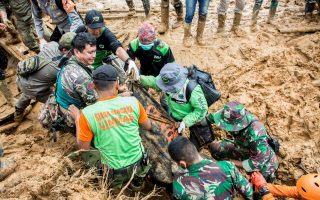 Rescue workers carry a body bag containing remains of victims following a landslide at Cisolok district in Sukabumi, West Java province, Indonesia, January 1, 2019 in this photo taken by Antara Foto. Picture taken January 1, 2019. Antara Foto/Nurul Ramadhan/ via REUTERS    ATTENTION EDITORS - THIS IMAGE WAS PROVIDED BY A THIRD PARTY. MANDATORY CREDIT. INDONESIA OUT.