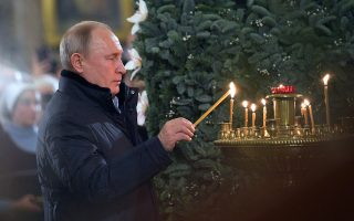 epa07266508 Russian President Vladimir Putin lights a candle during a Christmas service at the Cathedral of the Transfiguration of the Savior of All the Guards in St. Petersburg, Russia, 06 January 2019. The Russian Orthodox church celebrates Christmas on 07 January following the Julian calendar.  EPA/ALEXEI DRUZHININ / SPUTNIK / KREMLIN POOL SPUTNIK POOL