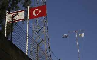 Turkish, right, and Turkish Cypriots breakaway flags are seen on the left as a Greek, left, and Cyprus' flags are seen on the right, on the abandoned military guard post at Pafos gate at the venetian wall that surrounds the old city of divided capital Nicosia, Cyprus, on Tuesday, July 4, 2017. At talks to end Cyprus' 43-year ethnic divide at the Swiss ski resort of Crans-Montana, Turkish Foreign Minister Mevlut Cavusoglu, made it clear that a peace accord would not include a specific, agreed-upon date by which all Turkish troops would have to be pulled out. (AP Photo/Petros Karadjias)