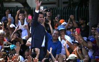 Venezuelan opposition leader Juan Guaido, who has declared himself the interim president of Venezuela, greets supporters as he arrives at a nationwide demonstration demanding the resignation of President Nicolas Maduro, in Caracas, Venezuela, Saturday, Feb. 2, 2019. Momentum is growing for Venezuela's opposition movement led by Guaido, who has called supporters back into the streets for nationwide protests Saturday, escalating pressure on Maduro to step down. (AP Photo/Fernando Llano)
