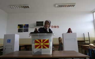 A woman casts her ballot at a polling station during a referendum in the village of Aracinovo, near Skopje, Macedonia, Sunday, Sept. 30, 2018. Macedonians were deciding Sunday on their country's future, voting in a crucial referendum on whether to accept a landmark deal ending a decades-old dispute with neighbouring Greece by changing their country's name to North Macedonia, to qualify for NATO membership and also pave its way toward the European Union. . (AP Photo/Boris Grdanoski)