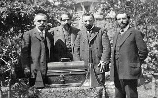 Οι Δ. Περιστέρης, Γ. Νάζος, Κ. Α. Ψάχος και Α. Μαρσίκ στη Ροδοδάφνη Αιγιαλείας, το 1910, σε επιτόπια έρευνα για συλλογή δημοτικών τραγουδιών. Έναν χρόνο πριν, η Ελληνική Λαογραφική Εταιρεία, με πρόεδρο τον Ν. Πολίτη και αντιπρόεδρο τον Γ. Νάζο, διευθυντή του Ωδείου Αθηνών, είχε αναλάβει πρωτοβουλία για την ηχογράφηση δημοτικών ασμάτων (Κέντρο Ερεύνης της Ελληνικής Λαογραφίας της Ακαδημίας Αθηνών).