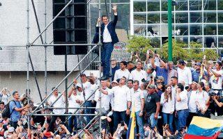 Ο Χουάν Γκουαϊδό, ανεβασμένος σε σκαλωσιά, χαιρετά τους οπαδούς του κατά τηνομιλία μετά την επιστροφή του από το εξωτερικό,στο Καράκας.