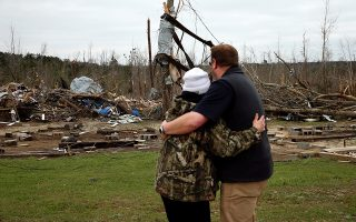 A man hugs Julie Morrison while looking at the remains of her home following a string of tornadoes that resulted in several fatalities in Beauregard, Alabama, U.S., March 4, 2019.   REUTERS/Elijah Nouvelage