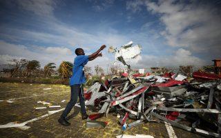 Ανδρας στοιβάζει μέταλλα που ξεκόλλησαν από κτίρια, λίγες μέρες μετά τις καταστροφές που προκάλεσε ο κυκλώνας Ιντάι. (REUTERS/Mike Hutchings)