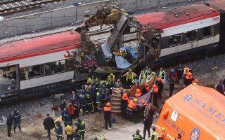 Άνδρες της πυροσβεστικής και των ομάδων διάσωσης καλύπτουν τις σωρούς των θυμάτων της τριπλής βομβιστικής επίθεσης της Αλ-Κάιντα εναντίον του προαστιακού σιδηρόδρομου της Μαδρίτης, το 2004. (AP Photo/Paul White)