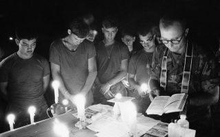 Σε μία στιγμή κατάνυξης και περισυλλογής, Αμερικανοί πεζοναύτες παρακολουθούν μία λειτουργία σε έναν αυτοσχέδιο βωμό που έχουν στήσει στο καπό ενός τζιπ, λίγο πριν εξαπολύσουν μία σφοδρή επίθεση εναντίον θέσεων των Βιετκόνγκ, νότια της πόλης της Ντα Νανγκ, στο Νότιο Βιετνάμ, το 1970. (AP Photo/Charles J. Ryan)