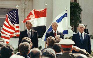 Με την αμερικανική, την αιγυπτιακή και την ισραηλινή σημαία να κυματίζουν από πίσω τους, ο πρόεδρος της Αιγύπτου, Ανουάρ Σαντάτ, ο Αμερικανός ομόλογος του, Τζίμι Κάρτερ, και ο Ισραηλινός πρωθυπουργός Μεναχέμ Μπέγκιν στέκονται σιωπηλοί κατά το άκουσμα των εθνικών ύμνων των ΗΠΑ, της Αιγύπτου και του Ισράηλ, λίγο πριν από την υπογραφή της Συνθήκης Ειρήνης Αιγύπτου - Ισραήλ, στον Λευκό Οίκο, η οποία είχε σκοπό την ομαλοποίηση των ταραγμένων σχέσεων των δύο χωρών, το 1979. (AP Photo)
