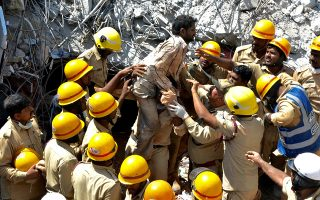 epa07456457 Indian Fire Brigade and National Disaster Response Force (NDRF) rescue workers pull a building worker from the site of a building collapse in Dharwad district North Karnataka around 430km from Bangalore, India, 22 March 2019. According to news report, at least 12 people were killed and several suspected to be trapped under the debris as a multi-storey under construction building collapsed on 19 March at Dharwad. Five bodies were recovered and two people were rescued on 21 March bringing to 61 the number of survivors so far.  EPA/STR