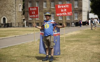 Anti-Brexit, pro-EU supporter Steve Bray holds placards on Abingdon Green across the road from the Houses of Parliament in London, Monday, July 9, 2018. Former U.K. Brexit Secretary David Davis said Monday that he won't seek to challenge Prime Minister Theresa May's leadership after resigning from her Cabinet, but will aim to pressure her to toughen her position on Britain's departure from the European Union. (AP Photo/Matt Dunham)