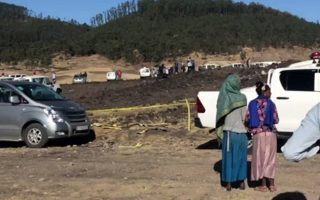In this image taken from video, people stand around the crash site of an Ethiopian Airlines flight that crashed shortly after takeoff lies at the scene at Hejere near Bishoftu, or Debre Zeit, some 50 kilometers (31 miles) south of Addis Ababa, in Ethiopia Sunday, March 10, 2019. The Ethiopian Airlines flight crashed shortly after takeoff from Ethiopia's capital on Sunday morning, killing all 157 on board, authorities said, as grieving families rushed to airports in Addis Ababa and the destination, Nairobi. (AP Photo)