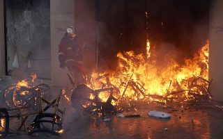 epa07442856 A fireman tries to extinguish a fire at  the burning luxury store Longchamps on the Champs Elysees during the 'Act XVIII' demonstration (the 18th consecutive national protest on a Saturday) in Paris, France, 16 March 2019. The so-called 'gilets jaunes' (yellow vests) is a grassroots protest movement with supporters from a wide span of the political spectrum, that originally started with protest across the nation in late 2018 against high fuel prices. The movement in the meantime also protests the French government's tax reforms, the increasing costs of living and some even call for the resignation of French President Emmanuel Macron.  EPA/YOAN VALAT