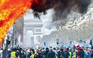 Κιόσκι πώλησης εφημερίδων και περιοδικών παραδομένο στις φλόγες –με φόντο την Αψίδα του Θριάμβου– κατά τη διάρκεια της διαδήλωσης των «Κίτρινων Γιλέκων» το περασμένο Σάββατο.