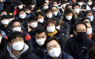 Workers wearing masks to protect from air pollution attend a rally against the government's labor policy in Seoul, South Korea, Wednesday, March 6, 2019. South Korean President Moon Jae-in has proposed a joint project with China to use artificial rain to clean the air in Seoul, where an acute increase in pollution has caused alarm. (AP Photo/Ahn Young-joon)