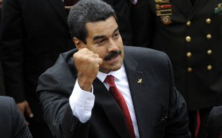 Venezuelan President Nicolas Maduro clenches his fist as he enters to the National Assembly before  the Presidential inauguration in Caracas on April 19, 2013. AFP PHOTO / LEO RAMIREZ