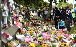 epa07444000 Members of the public place flowers at a makeshift memorial for the victims of the mosque mass murders at the Botanical Gardens in Christchurch, New Zealand, 17 March 2019. A gunman killed 50 worshippers at the Al Noor Masjid and Linwood Masjid on 15 March. A suspected gunman, 28-year-old Brenton Tarrant of Australia, has appeared in court on on the morning of 16 March and was charged with murder.  EPA/MICK TSIKAS  AUSTRALIA AND NEW ZEALAND OUT