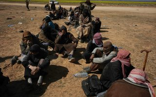 Men wait to be screened after being evacuated out of the last territory held by Islamic State militants outside Baghouz, Syria, Wednesday, March 6, 2019. Since Friday, IS has put up desperate resistance to renewed pounding by the U.S.-backed Syrian Democratic Forces aiming to take the tiny pocket on the Euphrates River near the Iraqi border.(AP Photo/Andrea Rosa)