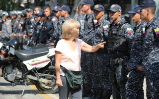 epa07448757 A woman speaks to members of the Bolivarian National Police (PNB), at the location where demonstrators planned to hold a march of public workers in Caracas, Venezuela, 19 March 2019. The PNB prevented Venezuelan public workers who support the head of Parliament, Juan Guaido, march to the seat of the Legislative, to which they demand to pass a law for the 'protection' of employees who 'defend' democracy.  EPA/RAUL MARTINEZ