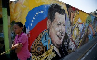 A woman waits by a mural of Venezuela's late President Hugo Chavez before entering the Historic Military Museum where Chavez's remains are buried, on the sixth anniversary of his death in Caracas, Venezuela, Tuesday, March 5, 2019. Chavez, who died of cancer, continues to unleash mixed feelings among Venezuelans: some remember him as the father of a revolution that defended the poor, while others blame him for the deep and prolonged crisis that overwhelms the South American country. (AP Photo/Eduardo Verdugo)