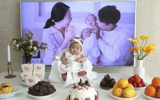 Αν και μόλις 3 μηνών είναι 2 ετών. Η εικονιζόμενη  Lee Yoon Seol κάθεται μεγαλοπρεπής για να συμμετάσχει με τον τρόπο της στους εορτασμούς που κανόνισαν οι γονείς της για την συμπλήρωση 100 ημερών από την γέννησή της. Η Yoon Seol γεννήθηκε παραμονή πρωτοχρονιάς και σύμφωνα με την Κορεατική παράδοση έγινε αυτόματα ενός έτους. Το πρόβλημα ξεκίνησε την επόμενη ημέρα καθώς σύμφωνα πάντα με την ίδια παράδοση κάθε πρωτοχρονιά όλοι οι κάτοικοι της χώρας φορτώνονται  ένα ακόμη χρόνο στην πλάτη τους. Ετσι το νεογέννητο έγινε μέσα σε μια σχεδόν ημέρα 2 ετών. Πολλοί κάτοικοι της χώρας ζητούν την κατάργηση του εθίμου ως αναχρονιστικό καθώς οι περισσότεροι έχουν άλλη ηλικία στην χώρα τους και μείον δύο έτη εκτός της. (AP Photo/Ahn Young-joon)