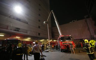 Firefighters work outside the scene of a fire at the Central World mall complex in Bangkok, Thailand, Wednesday, April 10, 2019. The fire had broken out in the Central World mall complex in Thailand's capital, with reports from emergency services saying it has caused a number of fatalities. (AP Photo/Sakchai Lalit)