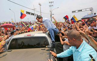 Ο αυτοανακηρυχθείς πρόεδρος της Βενεζουέλας Χουάν Γκουαϊδό σκαρφαλώνει σε αυτοκίνητο για να χαιρετήσει τους οπαδούς του.