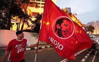 Οπαδός του προέδρου Τζόκο Ουιντόντο πανηγύριζε χθες την επανεκλογή του προέδρου σε δρόμο της Τζακάρτας.