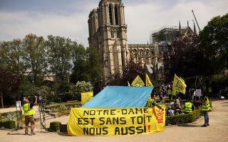 Πανό με σύνθημα «Η Νοτρ Νταμ είναι άστεγη, το ίδιο και εμείς!» από ακτιβιστές έξω από την καμένη εκκλησία, στη νήσο της Σιτέ.