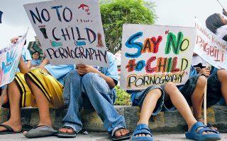 Πανό κατά της παιδικής πορνογραφίας κρατούν παιδιά στη Μανίλα, με αφορμή την Παγκόσμια Ημέρα του Παιδιού.