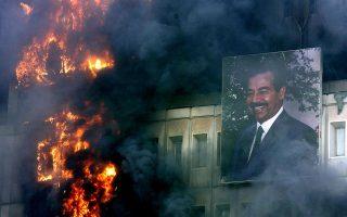 Το πορτρέτο του μέχρι πρότινος παντοδύναμου ηγέτη του Ιράκ, Σαντάμ Χουσείν, μοιάζει αδύναμο μπροστά στις φλόγες και τους πυκνούς καπνούς που αναδύονται από το το φλεγόμενο κτίριο του υπουργείου Μεταφορών και Επικοινωνιών, το οποίο δεν γλίτωσε από το πλιάτσικο και την οργή των πολιτών που ξεχύθηκαν στους δρόμους της Βαγδάτης μετά την εισβολή του αμερικανικού στρατού, το 2003. (AP Photo/Jerome Delay)