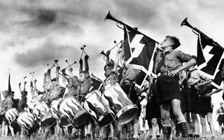 Γαλουχημένα άθελα τους με τα εθνικοσοσιαλιστικά ιδεώδη και τον ναζιστικό τρόπο ζωής, νεαρά αγόρια της μπάντας της Χιτλερικής Νεολαίας συμμετέχουν με θέρμη σε μία φιέστα του ναζιστικού καθεστώτος, κάπου στη Γερμανία, το 1935. (AP Photo)