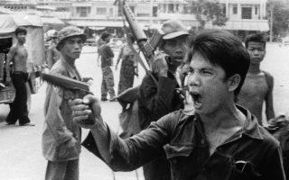 Με το όπλο του προτεταμένο και τον φανατισμό ζωγραφισμένο στον πρόσωπο του, ένας αντάρτης των Ερυθρών Χμερ διατάζει ορισμένους καταστηματάρχες να εγκαταλείψουν τα καταστήματα τους, λίγο μετά την κομμουνιστική κατάληψη της πρωτεύουσας της Καμπότζης, Πνομ Πεν, από τις κυβερνητικές δυνάμεις της του Βασιλείου της Καμπότζης, το 1975. (AP Photo/Christoph Froehder)