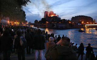 epa07508903 Parisians gather on the Seine river bank to look at the flames burning the roof of the Notre-Dame Cathedral  in Paris, France, 15 April 2019. A fire started in the late afternoon in one of the most visited monuments of the French capital.  EPA/IAN LANGSDON
