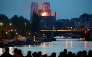 People watch as fire fighters douse flames of the burning NotreDameCathedral in Paris, France April 15, 2019. REUTERS/Charles Platiau