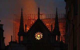 Flames and smoke rise from Notre Dame cathedral as it burns in Paris, Monday, April 15, 2019. Massive plumes of yellow brown smoke is filling the air above Notre Dame Cathedral and ash is falling on tourists and others around the island that marks the center of Paris. (AP Photo/Thibault Camus)