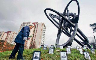 Γυναίκα αφήνει λουλούδια στο μνημείο των εργατών που πέθαναν από ραδιενέργεια μετά την έκρηξη του αντιδραστήρα.