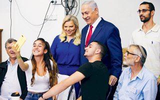 Ο πρωθυπουργός του Ισραήλ Μπέντζαμιν Νετανιάχου φωτογραφίζεται με τη σύζυγό του, αφού ψήφισαν στις χθεσινές εκλογές στην Ιερουσαλήμ. Η νύχτα έκρυβε εκπλήξεις, καθώς τα exit polls δεν έδειξαν σαφή νικητή. Ο Νετανιάχου φαίνεται να παραμένει στην εξουσία χάρη στην ενίσχυση των μικρών δεξιών κομμάτων, παρότι ο ίδιος μοιάζει να χάνει από τον «κυανόλευκο» συνασπισμό του πρώην στρατηγού Μπένι Γκαντς.
