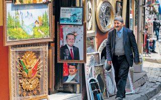 Πολίτης περνάει μπροστά από κατάστημα με κορνίζες στο κέντρο της Κωνσταντινούπολης. Στην είσοδο δεσπόζει το πορτρέτο του Ταγίπ Ερντογάν πάνω από αυτό του Τουργκούτ Οζάλ. EPA/SEDAT SUNA