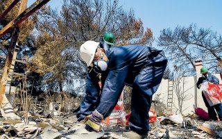 Υπάλληλοι ειδικού συνεργείου απομακρύνουν, πέρυσι τον Αύγουστο, υλικά από αμίαντο από καμένο σπίτι στο Μάτι.