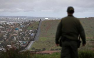 FILE - In this Feb. 5, 2019, file photo, Border Patrol agent Vincent Pirro looks on near a border wall that separates the cities of Tijuana, Mexico, and San Diego, in San Diego. U.S. border authorities say they've started to increase the biometric data they take from children 13 years of age and younger, including fingerprints and DNA samples, despite privacy concerns and government policy intended to restrict what can be collected from migrant youth. (AP Photo/Gregory Bull, File)