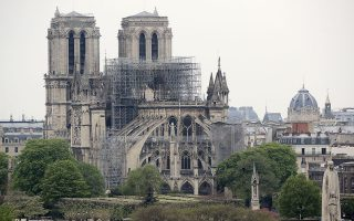 epa07509655 The statue of Saint Genevieve (front), Patron Saint of Paris, on le Pont de la Tournelle bridge, rises near the damaged Notre-Dame Cathedral after a massive fire that destroyed its roof in Paris, France, 16 April 2019. View from the Arab World Institute. A fire started in the late afternoon 15 April in one of the most visited monuments of the French capital.  EPA/CHRISTOPHE PETIT TESSON