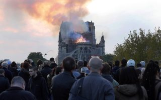 FILE - In this Monday, April 15, 2019 file photo, people watch as flames and smoke rise from Notre Dame cathedral in Paris. On Friday, April 19, 2019, The Associated Press has found that stories circulating on the internet that a Muslim woman in Paris was arrested for planning a terrorist attack at the cathedral, days before the fire, are untrue. French judicial official said Thursday that investigators believe the fire started because of an electrical problem. (AP Photo/Thibault Camus)