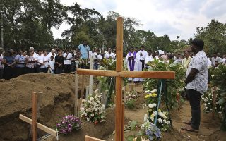 A priest conducts funeral service for a victim of Easter Sunday's bomb blast at St. Sebastian Church, in Negombo, Sri Lanka Thursday, April 25, 2019. The U.S. Embassy in Sri Lanka warned Thursday that places of worship could be targeted for militant attacks over the coming weekend, as police searched for more suspects in the Islamic State-claimed Easter suicide bombings that killed over 350 people. (AP Photo/Manish Swarup)