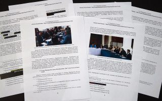 Special counsel Robert Mueller's redacted report on the investigation into Russian interference in the 2016 presidential election is photographed Thursday, April 18, 2019, in Washington. The photos in the report show George Papadopoulos and others in meetings. (AP Photo/Jon Elswick)