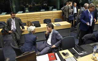 Greek Finance Minister Euclid Tsakalotos. center right, speaks with Managing Director of the International Monetary Fund Christine Lagarde, center left, during a round table meeting of eurogroup finance ministers at the EU Lex building in Brussels on Sunday, July 12, 2015. Greece has another chance Sunday to convince skeptical European creditors that it can be trusted to enact wide-ranging economic reforms which would safeguard its future in the common euro currency. (AP Photo/Michel Euler)