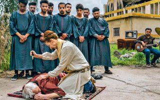 Ο Αγαμέμνων νεκρός, με φόντο τα χαλάσματα της Μοσούλης. Ερασιτέχνες ηθοποιοί, κάτοικοι της βασανισμένης ιρακινής πόλης που αποτέλεσε προπύργιο των μαχητών του Ισλαμικού Κράτους, συμμετέχουν στην πρωτοποριακή παράσταση «Ορέστης στη Μοσούλη», διασκευή της τριλογίας του Αισχύλου «Ορέστεια». Ο Ελβετός σκηνοθέτης Μίλο Ράου μιλάει στην «Κ» για το έργο του, την καθαρτήρια δύναμη της αρχαίας τραγωδίας και τη δυνατότητα για συγχώρηση. (Φωτ. Sergey Ponomarev/NYTimes)