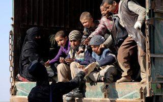Μαχητής των υπό κουρδικό έλεγχο Συριακών Δημοκρατικών Δυνάμεων μοιράζει ψωμί σε παιδιά, κοντά στο Μπαγούζ της επαρχίας Ντέιρ αλ Ζορ.