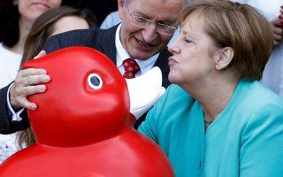 Φιλιά. Την εταιρία βιοτεχνολογίας Centogene στο Rostock επισκέφθηκε η καγκελάριος της Γερμανίας, Αγγελα Μέρκελ. Εκεί έλαβε σαν δώρο ένα υπερμέγεθες, πλαστικό, κόκκινο παπάκι.  REUTERS/Michele Tantussi